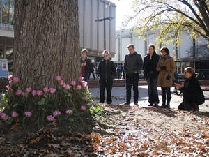 A group of on lookers pay their respects to those who have been persecuted because of their gender on Transgender Remembrance day, Wednesday afternoon in the Pit.