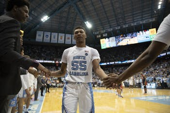 UNC graduate guard Christian Keeling (55) shakes hands with his teammates after the loss against Virginia at the Smith Center on Saturday, Feb. 15, 2020.