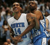 Former UNC players Danny Green (left) and Vince Carter goof off during a foul shot during UNC's alumni game Friday night.