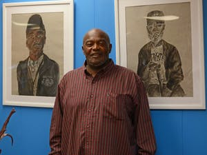 Anthony Sharp stands next to artwork at the CEF office - he is currently organizing an art show with the office to be featured in the Ackland and Campus Y in April.