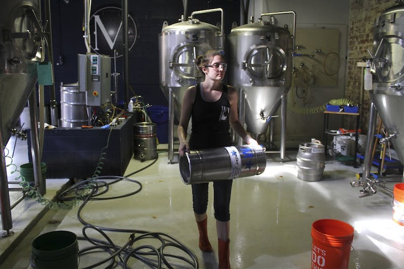 22 companies collaborated this weekend to create the North Carolina state beer at Mystery Brewing Company in Hillsborough. Erica Tieppo, from Detroit, Michigan, works with the beer through its fermentation process.
