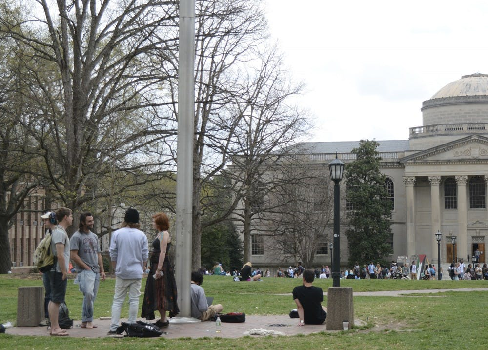 Students smoke and converse around the flagpole on the Lower Quad.