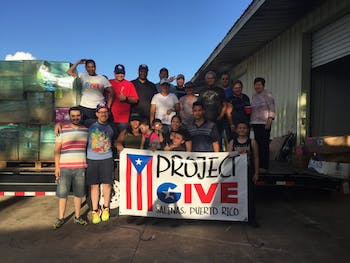 Members of the groups pose together in front of the food and supplies they've gathered for Puerto Rico. Photo courtesy of Jose Cartagena.