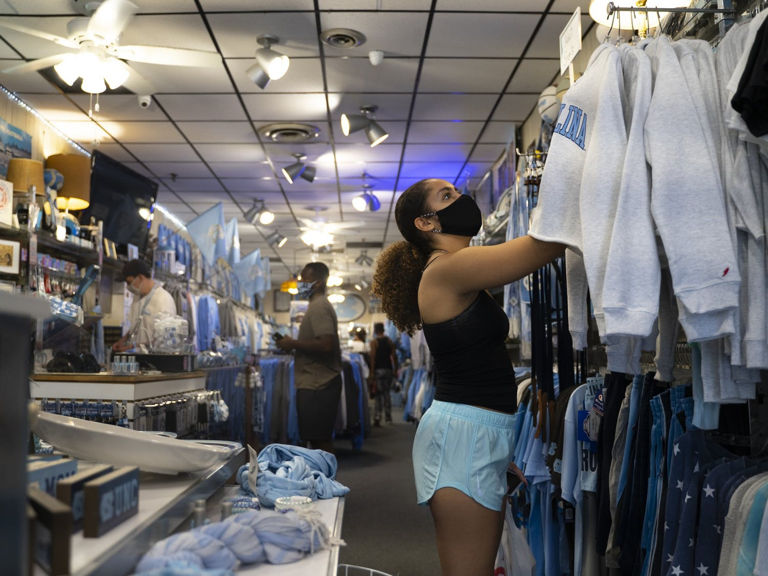 First-years Kambree Vincent (front) and Shawn Williamson (behind) shop for UNC apparel at Carolina Pride on Franklin Street on Thursday, Aug. 6, 2020.