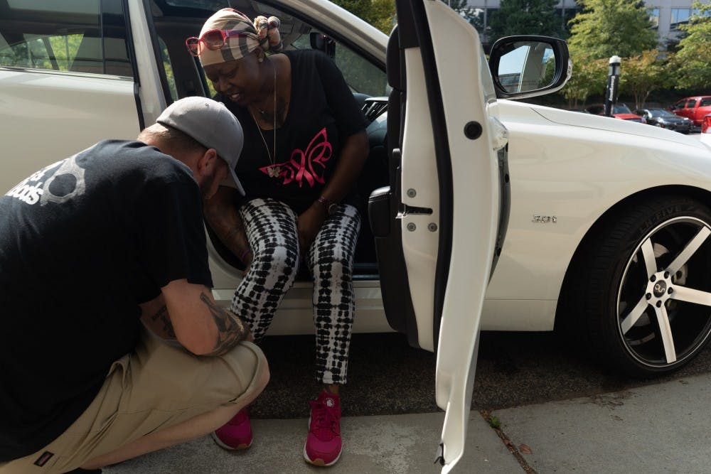 <p>Scott Reece, 45, helps his wife, Nunny Reece, 41, who has stage 4 metastatic breast cancer, tie her shoes on Tuesday, Oct. 1, 2019. Nunny Reece and her husband frequent UNC Hospital often and face additional challenges due to parking costs, which typically are up to $10 a day. On this day, Reece had a parking permit due to her receiving radiation treatment all week.&nbsp;</p>