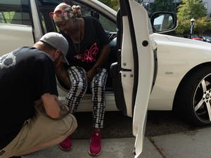 Scott Reece, 45, helps his wife, Nunny Reece, 41, who has stage 4 metastatic breast cancer, tie her shoes on Tuesday, Oct. 1, 2019. Nunny Reece and her husband frequent UNC Hospital often and face additional challenges due to parking costs, which typically are up to $10 a day. On this day, Reece had a parking permit due to her receiving radiation treatment all week.