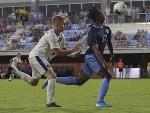UNC first-year forward Key White (13) races to beat Creighton University's sophomore midfielder Keegan Boyd (17) to gain possession during Friday night's 2-2 tie.