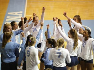 The women's volleyball team huddles before a game against LIU Brooklyn on Sep. 8.