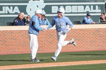 Sophomore Michael Busch (15) shakes hands with head coach Mike Fox as he runs the bases after a home run against Florida State on March 23, 2018.