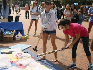 Amanda Roth (left) and Emili Hall, both juniors, participate in Southern Smash, an event hosted by UNC Panhellenic Council that allows participants to break scales that represent the things that weigh them down.
