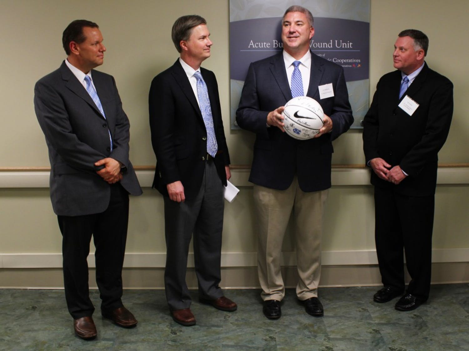 """(L to R) Dr. Bruce Cairns, director of the North Carolina Jaycee Burn Center, Chancellor Holden Thorp, associate athletic director Rick Steinbacher, and Dale Lambert, chief executive officer of Randolph Electric Membership Corporation, helped present the new """"Acute Burn and Wound Unit"""" , part of UNC Hospital's East Wing, on Thursday afternoon.The basketball held by Steinbacher was signed by Roy and basketball players (double check w/ writer). Presented to nurse managers of burn unit."""