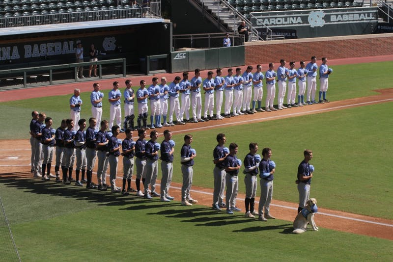 The North Carolina baseball team stands for the national anthem before its Fall World Serie intrasquad scrimmage on Sunday afternoon.