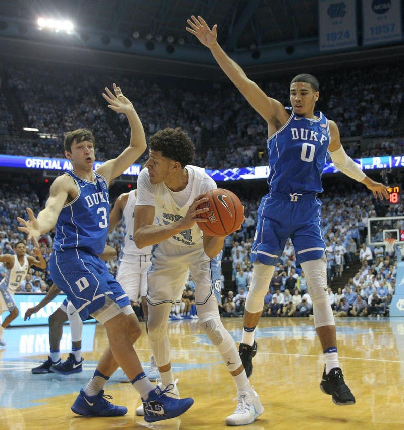 North Carolina wing Justin Jackson (44) attempts to pass around a Duke double team Saturday night.