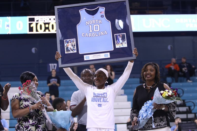 Jamie Cherry, the lone senior on the 2017-18 women's basketball team, holds up a framed jersey on UNC's senior night on Feb. 20 in Carmichael Arena.