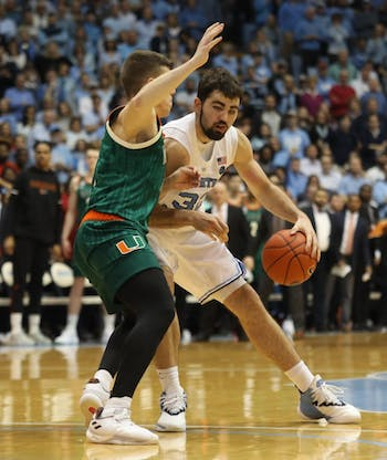 Miami junior guard Dejan Vasiljevic (1) guards UNC senior forward Luke Maye (32) on Saturday, Feb. 9, 2019 in the Smith Center. UNC men's basketball defeated Miami 88-85 in overtime.
