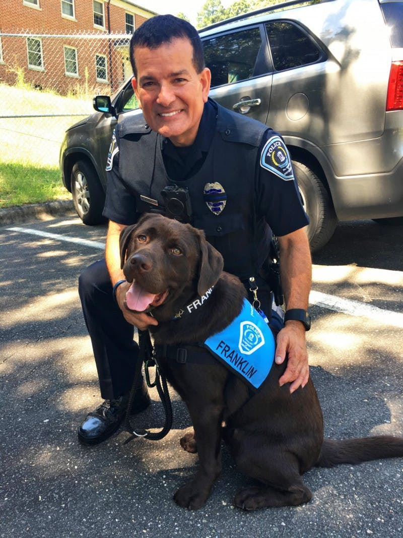 Franklin the dog poses with UNC Police Officer Ray Rodriguez on campus. Photo by Officer Rodriguez.