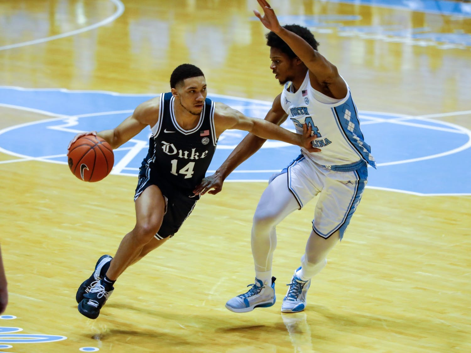 Duke senior guard Jordan Goldwire (14) dribbles past UNC first year guard Kerwin Walton (24) during a game against Duke in the Smith Center on Saturday, March 6, 2021.
