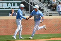 UNC outfielder Brian Holberton (10) celebrates with head coach Mike Fox after Holberton hit a solo home-run in the 5th inning.