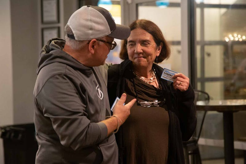 """Steve Friedman, a candidate for the Carrboro Board of Alderman, thanks Jacquelyn Gist, a current member of the Carrboro Board of Alderman, with a patch on Nov. 5, 2019 at the Craftboro Brewing Depot. Friedman says that, """"patches are special because you can't buy them, you have to earn them.""""  The polls put him at 13 percent."""