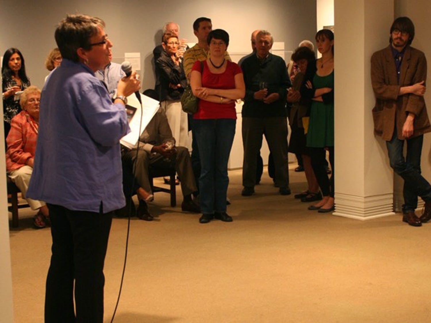 Amanda Hughes, director of external affairs, welcomes the crowd Friday at the Ackland Art Museum to the exhibition featuring Andy Warhol Polaroids.