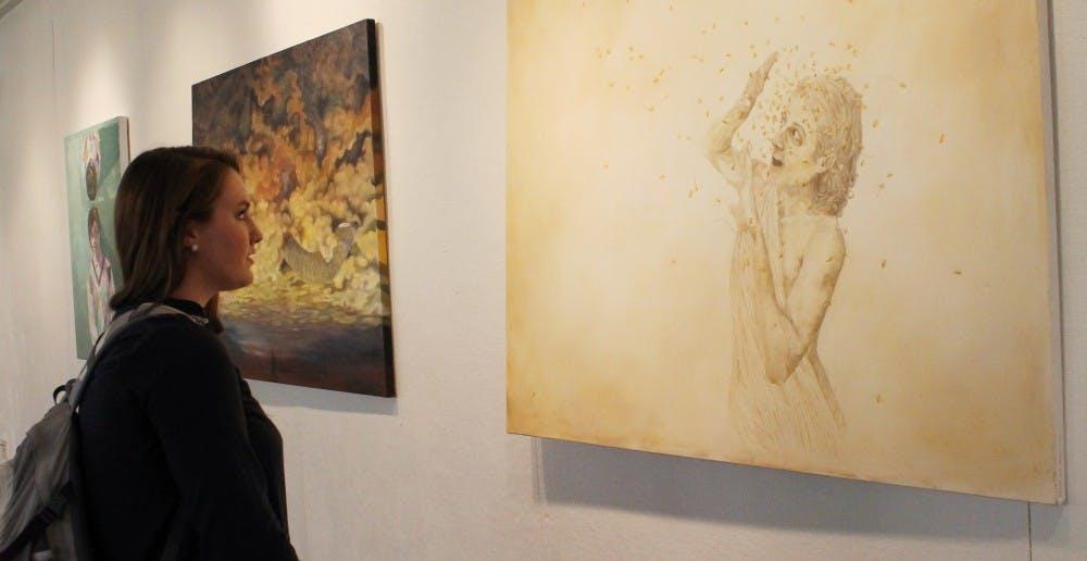 Reagan Toal, a freshman English major from Charlotte, North Carolina, enjoys looking at the artwork on display.