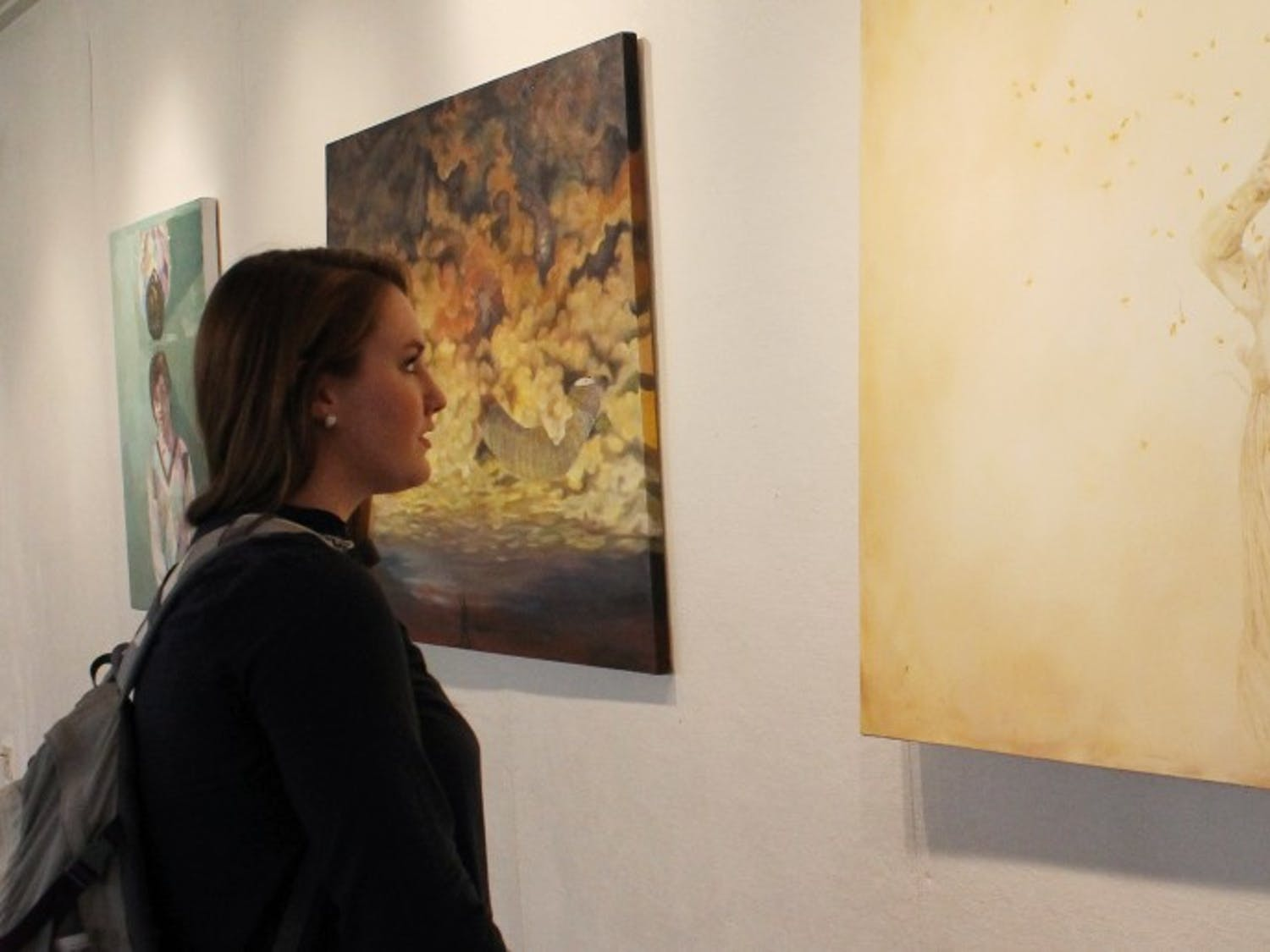 Reagan Toal, a freshman English major from Charlotte, North Carolina, enjoys looking at the artwork on display.