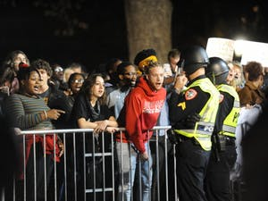 A protestor shouts at police officers during a protest against Chancellor Carol Folt and the Board of Trustees' proposal for the Silent Sam's relocation in McCorkle Place on Monday, Dec. 3, 2018.
