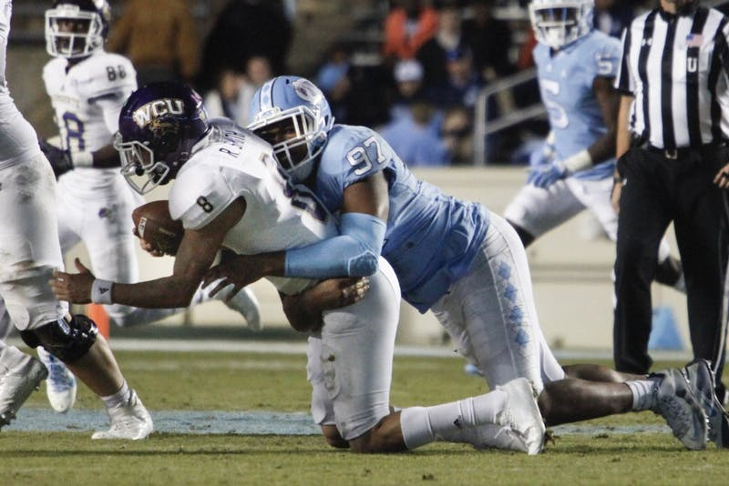 Defensive tackle Jalen Dalton (97) makes a tackle against Western Carolina on Saturday in Kenan Stadium.