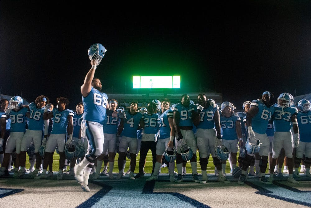 UNC graduate offensive lineman Brian Anderson (68) lifts his helmet in celebration of the Tar Heel football team's win against the University of Virginia. UNC defeated the Cavaliers 59-39, their second win of the season.