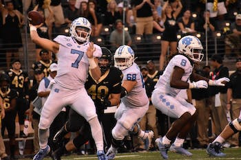 UNC-CH first-year quarterback Sam Howell (#7) winds up a throw to one of his teammates as the Wake Forest defense closes in.