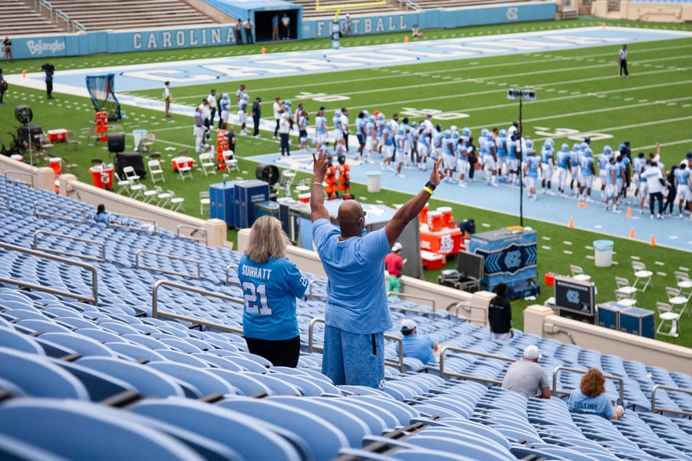 <p>Parents of UNC graduate student and linebacker Chazz Surratt Brandi and Kevin Surratt cheer from the stands of Kenan Memorial Stadium during a game against Syracuse on Saturday, Sept. 12, 2020. UNC beat Syracuse 31-6.&nbsp;</p>