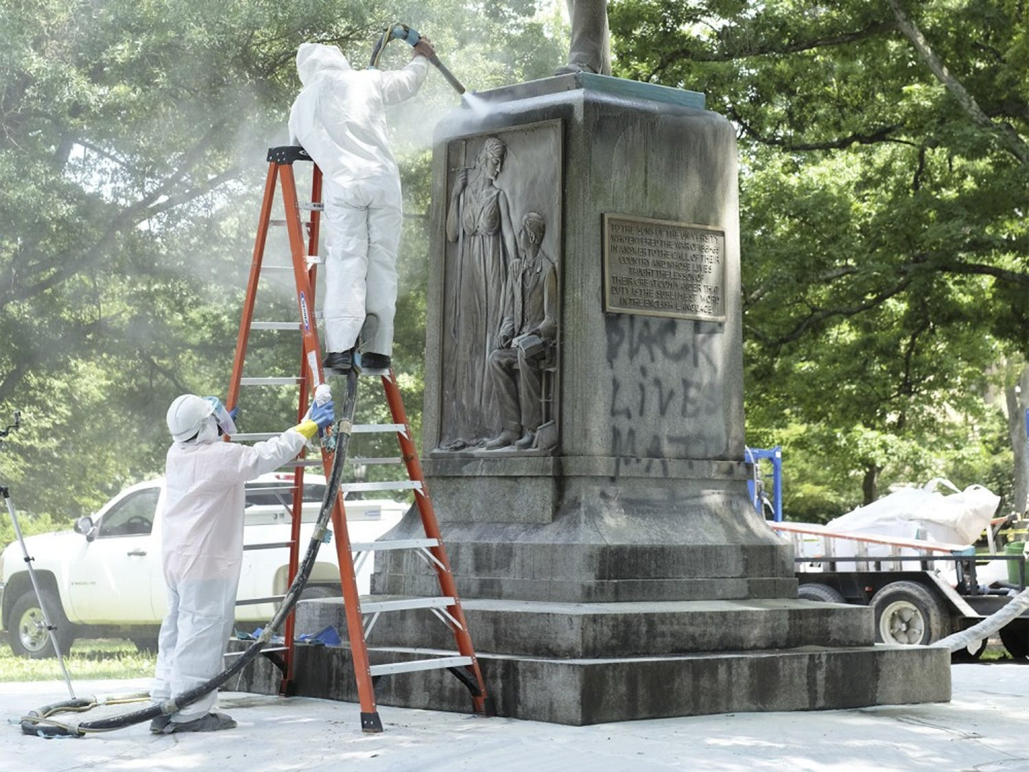 """Workers clean the Silent Sam memorial on campus after it was spray painted in July 2015. The memorial was painted with """"black lives matter."""""""