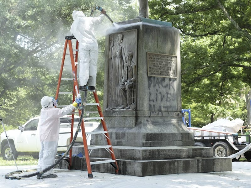 "Workers clean the Silent Sam memorial on campus after it was spray painted in July 2015. The memorial was painted with ""black lives matter."""