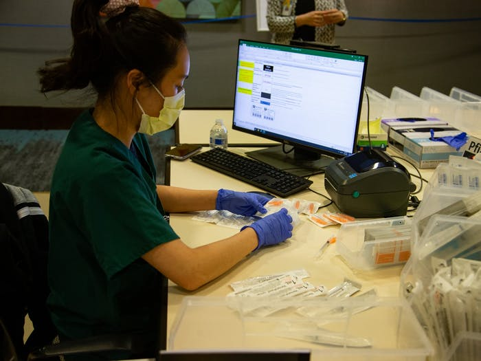 Fourth year pharmacy student Hannah Kim prepares syringes at the end of a day of of vaccinations at the Friday Center on Monday, Mar. 22, 2021.
