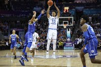 Duke first-year guard Tre Jones (3) attempts to block a three-pointer by UNC graduate guard Cameron Johnson (13) during the semifinals of the ACC Tournament at the Spectrum Center in Charlotte, N.C. on Friday, March 15, 2019. UNC fell to Duke 73-74.