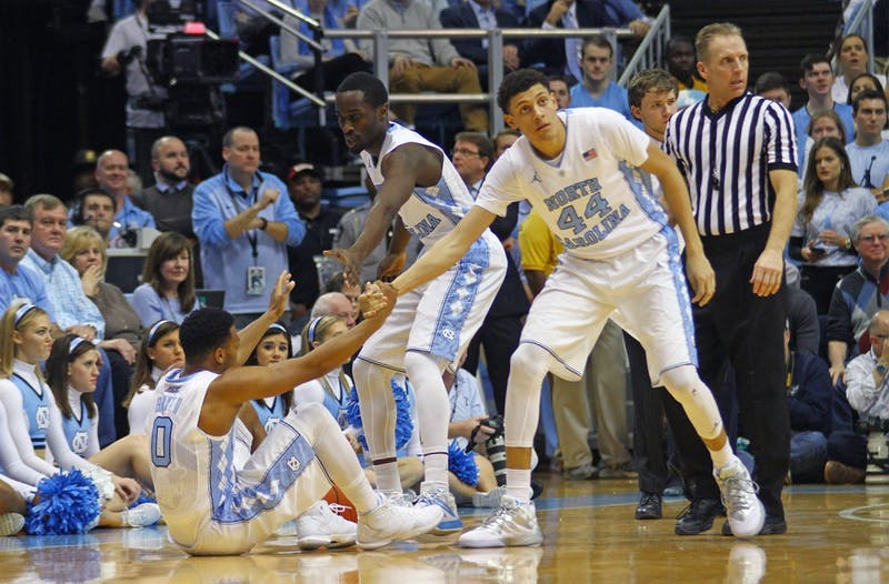Forward Justin Jackson (44) and guard Theo Pinson (1) help up guard Nate Britt (0) during the game against N.C. State on Jan. 16.