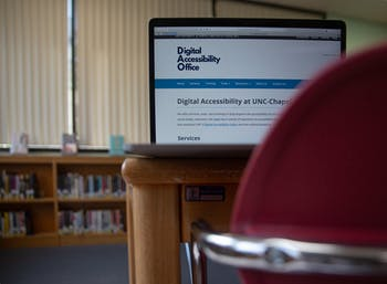DTH Photo Illustration. A computer screen shows the homepage for UNC's Digital Accessibility Office. The DAO offers training, consulting and resources to ensure that digital materials are available to students.
