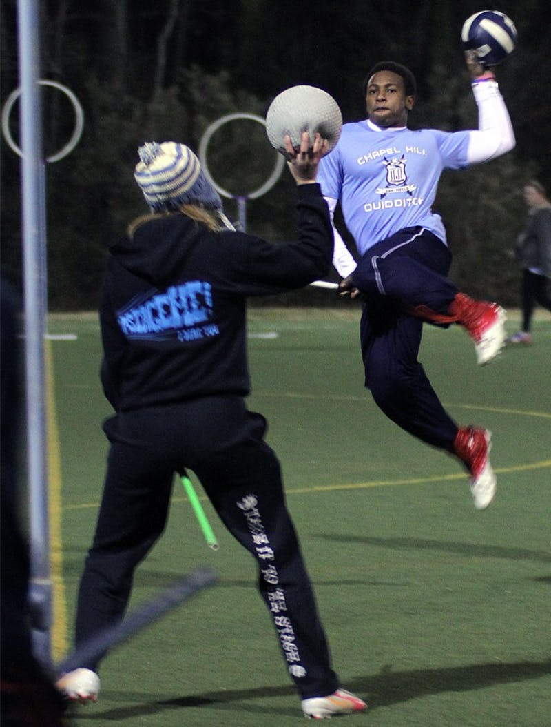 Lee Hodge jumps before attempting to score while Jessica McAfee defends during a Wednesday night quidditch practice.