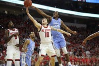 UNC guard Kenny Williams (24)  attempts to block a shot from NC State guard Braxton Beverly (10) in PNC Arena Tuesday, Jan. 8, 2019. UNC defeated NC State 90-82.