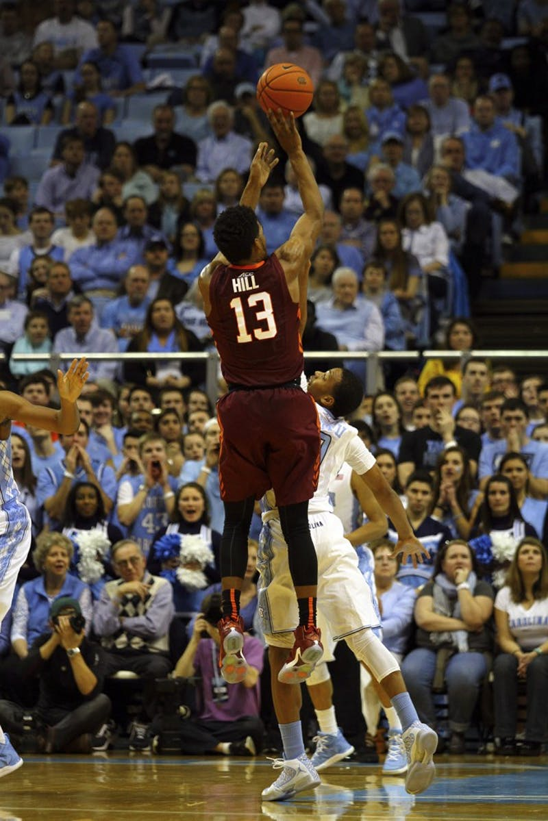 UNC sophomore guard Nate Britt (0) blocks Virginia Tech freshman guard Ahmed Hill (13) from making a three-pointer.