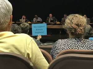 Community members holding signs at the Monday, May 20 Board of Education meeting for Orange County.