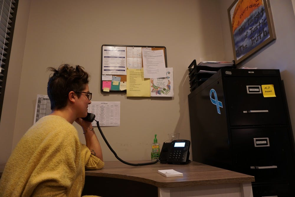 <p>Rachel Valentine, executive director for the Orange County Rape Crisis Center in Chapel hill, answers the phone in an office designated for first responses to clients on Wednesday, Jan. 16, 2019.</p>