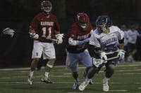 UNC's Ryan Creighton (33) scoops a ground ball and looks up the field.