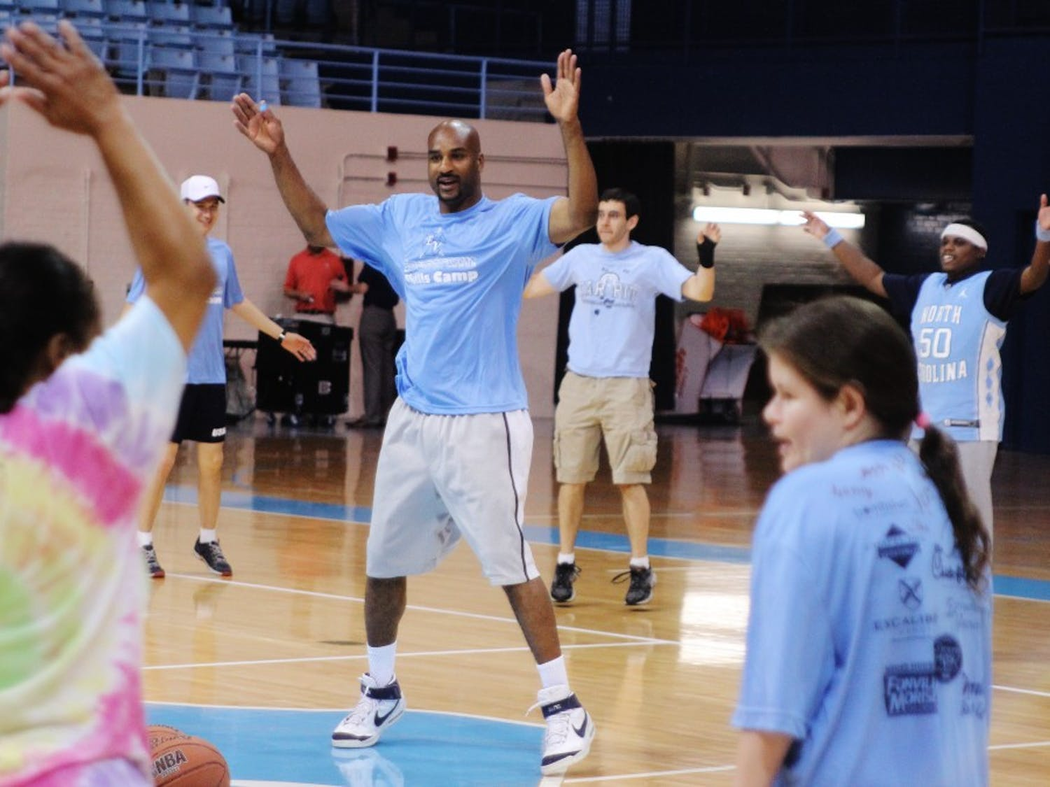 Basketball game for autistic kids at Carmichael ArenaIn the center, Roger Hudson, a Tar Heel volunteer who studied Political Policy and graduated in 1996, is leading the kids for some warm-up exercises.