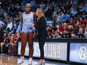 UNC's women's basketball coach Courtney Banghart talks with junior center Janelle Bailey (30) during a game against N.C. State on Thursday, Jan. 9, 2020. UNC broke NC State's undefeated streak with a score of 66-60.