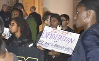 A coalition of students protest and interrupt Carol Folt at a meeting at town hall on Nov. 19, 2015. They read a list of demands that call for change at universities worldwide.