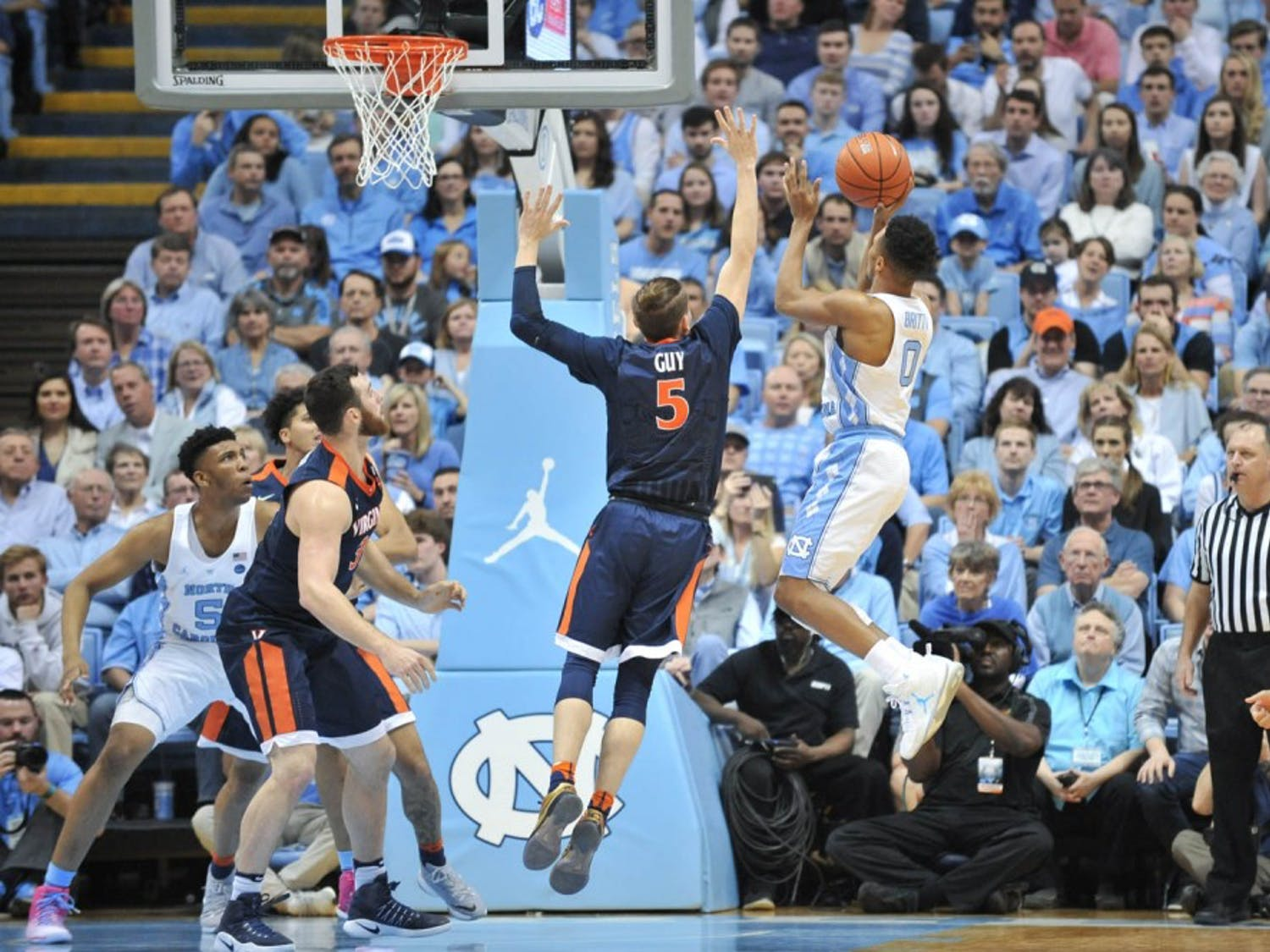 Senior Nate Britt (0) goes up for a shot against a UVA defender on Saturday night.
