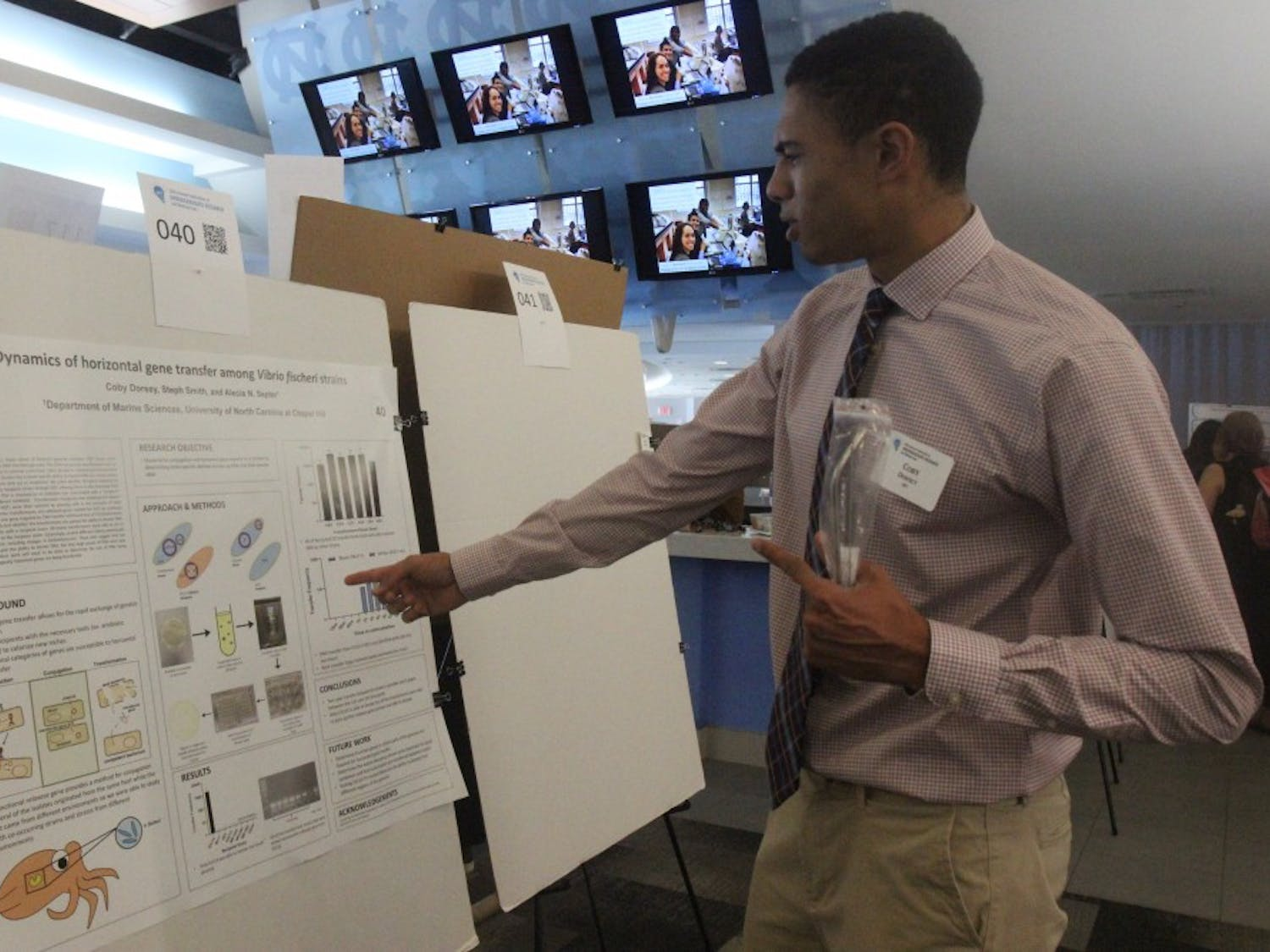 """Sophomore chemistry major Coby Dorsey presents his research on Sahar Khalifeh's novel """"Wild Thorns"""" at the 20th annual Celebration of Undergraduate Research and Making Expo on Wednesday April 24, 2019 in the Blue Zone in Kenan Stadium."""