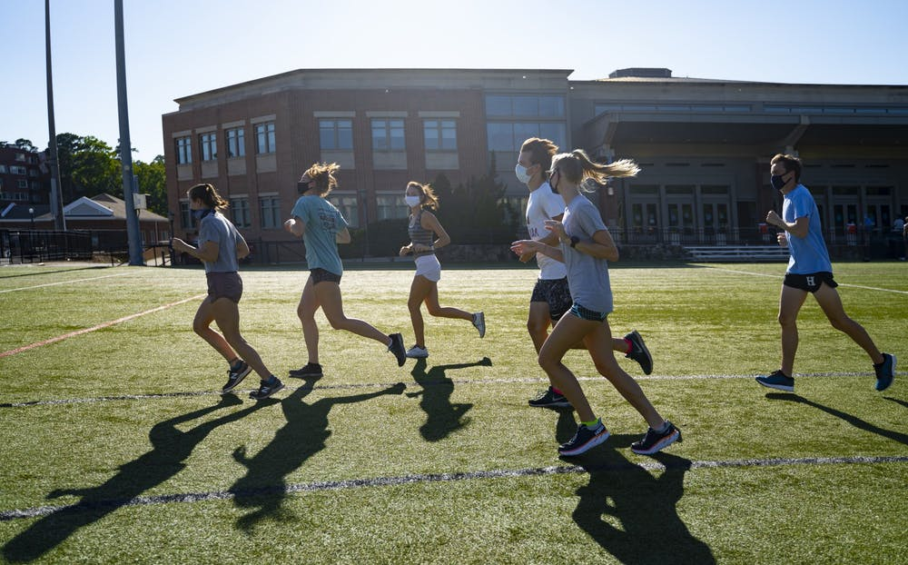 <p>Members of UNC Running club run together in masks across Hooker Fields to warm up on Friday, Sept. 4, 2020. They are happy to be able to continue practicing together with new precautions in place amid the COVID-19 pandemic.</p>
