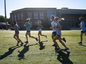 Members of UNC Running club run together in masks across Hooker Fields to warm up on Friday, Sept. 4, 2020. They are happy to be able to continue practicing together with new precautions in place amid the COVID-19 pandemic.